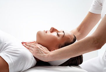Reiki therapy being performed on a woman who is laying down