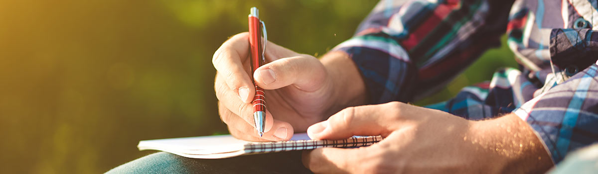 Man writing in notebook in nature